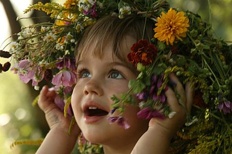 Фото Девочка придерживает руками огромный венок из полевых цветов на голове