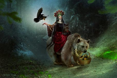 Фото Черноволосая колдунья, сидящая верхом на медведе с ожерельем из ключей на шее, держащего в зубах плетеную корзинку с черепами, бредущим по лесной тропинке, над рукой у девушки парит черный ворон со светящимся кулоном на шее, на руке сидит черный кот, автор Briet Olga