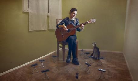 Фото Кошка слушает игру девочки на гитаре