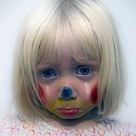 Фото Разрисованное цветными красками обиженное лицо девочки, с голубыми глазами