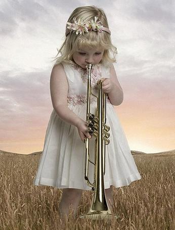 Фото Девочка дует в музыкальную трубу
