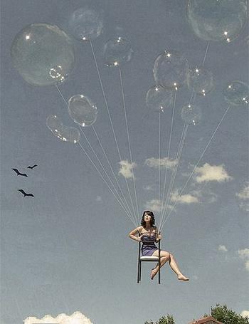 Фото Девушка поднимается в небо на стуле, привязанном к большим мыльным пузырям