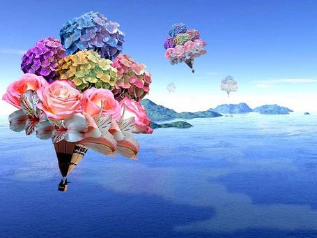 Фото Воздушные шары из цветов с корзинами, в которых сидят люди, летят над морем и горами