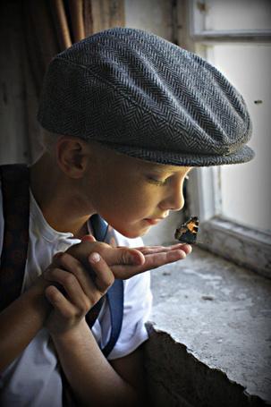 Фото На пальце руки мальчика сидит бабочка