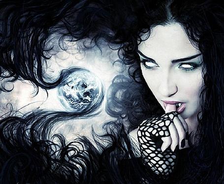 Фото Девушка с белыми глазницами, развевающимися черными волосами на фоне неба, держит палец руки в черной перчатке у себя во рту