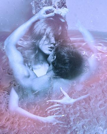 Фото Мужчина обнимает девушку на фоне неспокойных морских волн