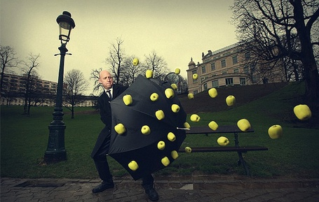 Фото Мужчина на улице города закрывается от летящих в него зеленых яблок раскрытым зонтиком, фотограф Ronen Goldman