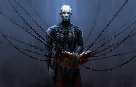 Фото Мужчина закованный в цепи держит руку на книге
