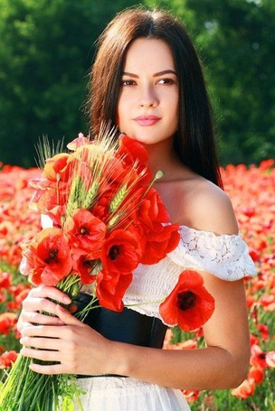 Фото Девушка держит в руках букет красных маков