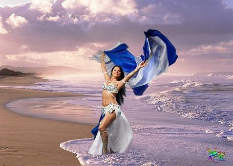 Фото Девушка танцует восточный танец на берегу моря, стоя в воде
