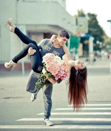 Фото Парень идет по пешеходному переходу и несет девушку на руках. Счастливая девушка держит рукой парня за шею. Она откинула голову назад и держит в руках большой букет цветов
