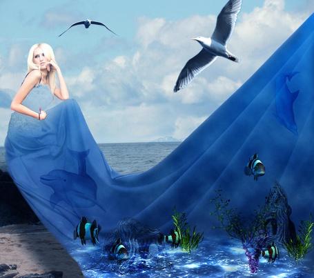 Фото Девушка блондинка сидит на берегу моря в длинном голубом платье, на котором изображен подводный мир с рыбами, дельфинами, водорослями, у нее над головой летают чайки