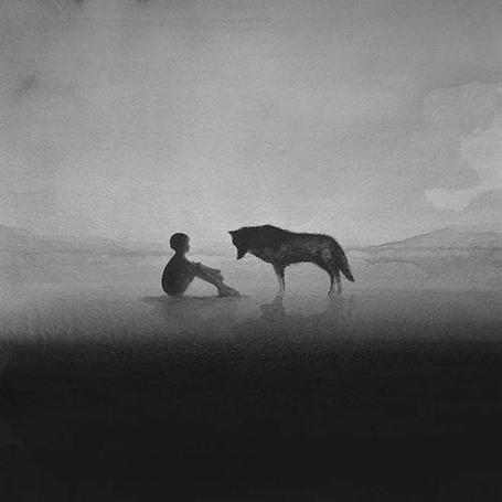 Фото Мальчик сидит на земле, смотря на волка, опустившего голову