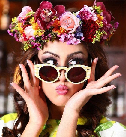 Фото Девушка в веночке из цветов на голове, придерживает солнцезащитные очки на лице двумя руками, при этом сделав губы бантиком