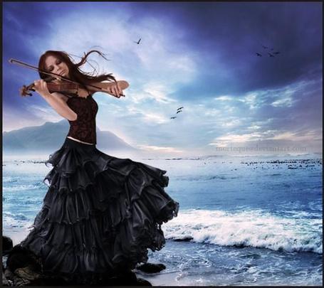 Фото Девушки играет на скрипке на берегу моря