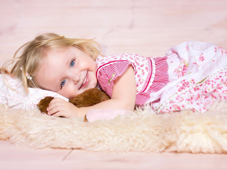 Фото Улыбающаяся девочка лежит на кровати в обнимку с игрушкой
