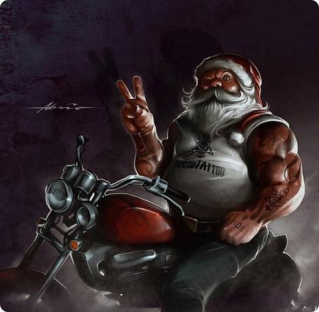 Фото Санта Клаус байкер, в майке, с тату, сидит на байке и поднял вверх два пальца, Victoria (Победа)