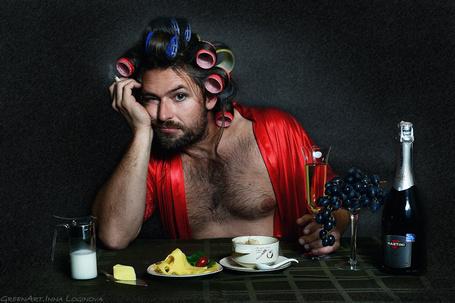 Фото Грустный мужчина сидит за столом в бегудях на фоне шампанского, винограда и чашечки