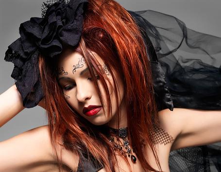 Фото Грустная девушка с рыжими волосами с тату на лице