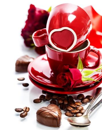 Фото Две кружки с блюдцами, красная роза, кофейные зерна и конфеты в виде сердец