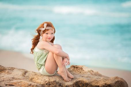 Фото Девочка сидит на камне у моря