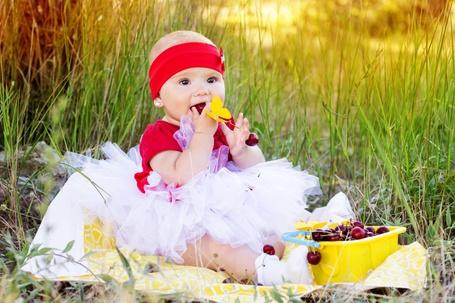 Фото Красивая девочка сидит на полянке и кушает черешню