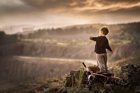 Фото Мальчик стоит на велосипеде на фоне огромного панорамного вида природы, ву igrudzien