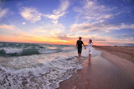 Фото Вдоль берега моря по набегающей морской волне идут мужчина и девушка. На заднем плане закат солнца. Фотограф Андрей Кривцов