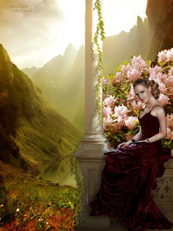 Фото Красивая девушка в длинном платье среди цветов на фоне гор и древнего замка сидит на бордюрчике балкона