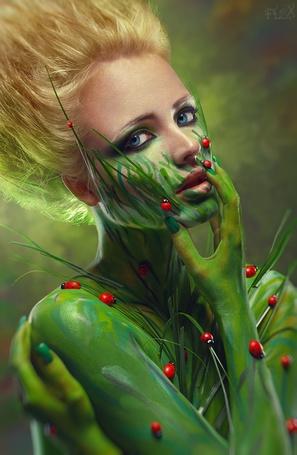 Фото Девушка блондинка с голубыми глазами разрисованная зелеными красками с божьими коровками на теле