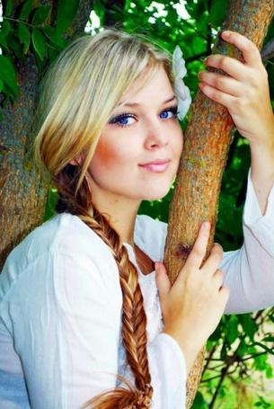 Фото Красивая голубоглазая девушка стоит возле дерева