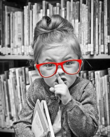 Фото Девочка в очках приложила палец к губам, призывая к тишине