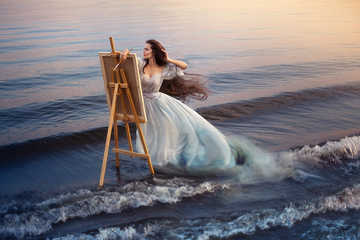 Фото Девушка в белом платье с мольбертом стоит на берегу моря среди набегающих на берег волн, фотограф Екатерина Ромакина