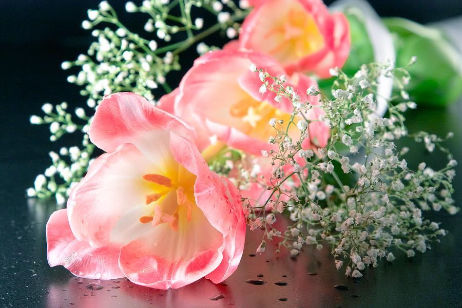 Букет из розовых тюльпанов и белых мелких цветов лежит на стеклянной поверхности. Фотограф Юлия Стрюкова