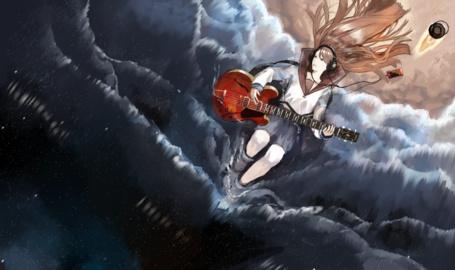Фото Девушка в наушниках с гитарой лежит на пляже