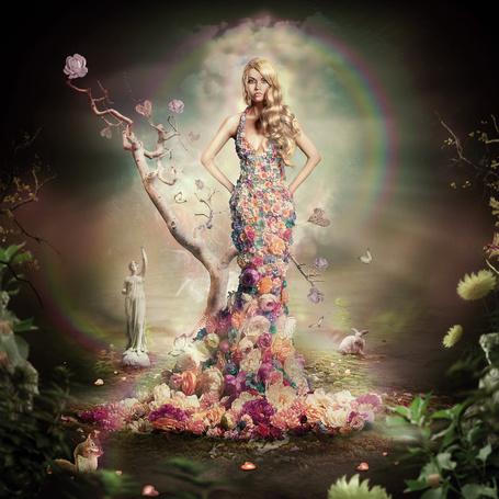 Фото Девушка в платье из цветов стоит на фоне радуги, статуи, белочки и кролика