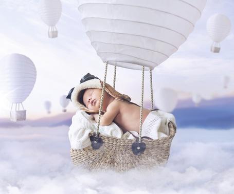 Фото Малыш спит лежа на воздушном шаре, который парит среди облаков