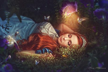 Фото Девушка лежит в траве под светящимся цветком