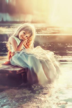 Фото Милая девочка сидит на мостках в лучах солнца