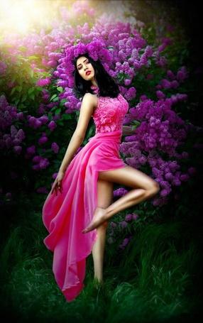 Фото Девушка с длинными черными волосами в ярком светло-красном платье и в венке из цветов сирени стоит, приподняв ногу, рядом с кустом цветущей сирени. Визаж Анастасия Комарова