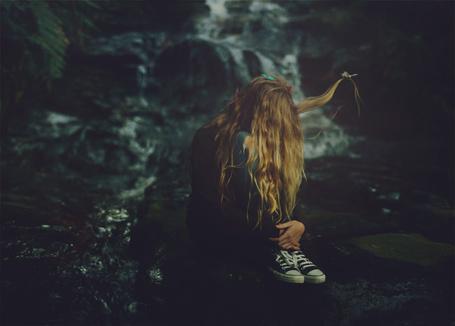 Фото Грустная девушка сидит на земле, на волосах у нее сидят бабочки