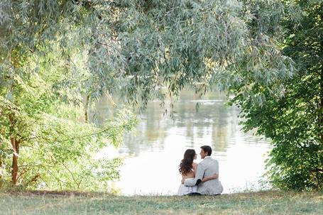 Фото Парень и девушка сидят обнявшись у водоема и смотрят друг на друга