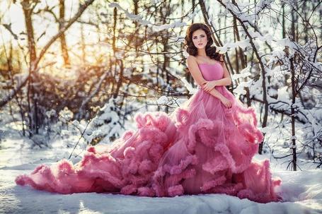 Фото Девушка в шикарном ярко-розовом платье стоит среди снега, положив одну руку на другую, на заднем плане заснеженные деревья, фотограф Илья Двояковский