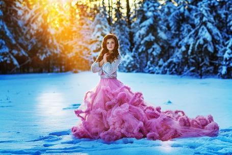 Фото Девушка в шикарном ярко-розовом платье и в светлой кофточке стоит среди снега, сложив руки на груди, на заднем плане сквозь заснеженные деревья пробиваются лучи солнца, фотограф Илья Двояковский