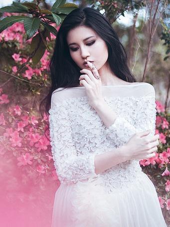 Фото О чем то задумавшаяся красивая восточная девушка модель Gan Lu, стоит на фоне цветущего розовыми цветами куста