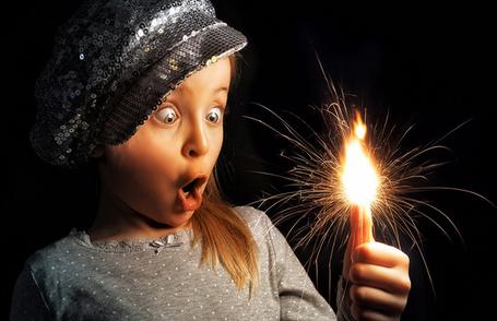 Фото Девочка с удивлением и восторгом смотрит на бенгальский огонь