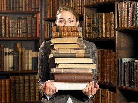 Фото Девушка библиотекарь с кипой тяжелых книг