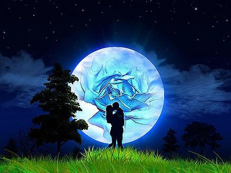 Фото Темные силуэты парня и девушки, целующихся на фоне огромной луны с изображением голубой розы