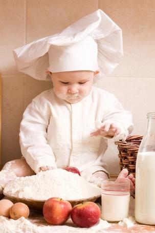 Фото Ребенок в одежде повара возится с продуктами