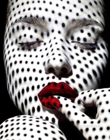 Фото На лицо девушки с красными губами падает тень в горошек
